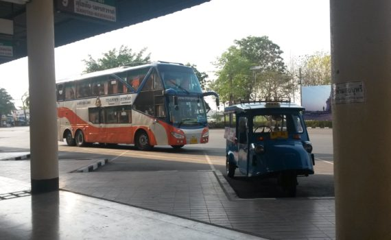 Reisebus mit Tuk Tuk im Vordergrund