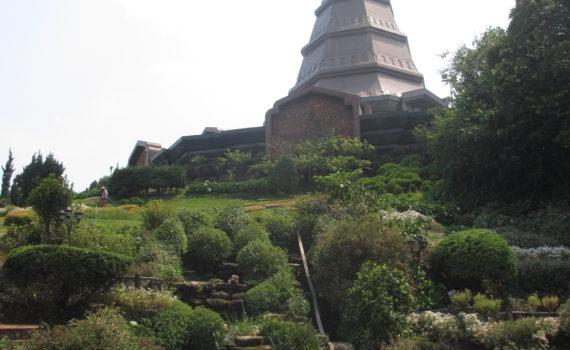 Die Königspagode liegt auf einem Hügel umrundet von zahlreichen Blumen. In der Pagode findet man einen Buddah.